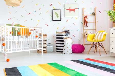 Baby room with yellow chair and white cot Standard-Bild - 68553754