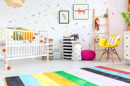 Sitio del bebé con la silla amarilla y cuna blanco Foto de archivo - 68553754