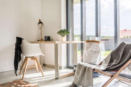 Sala blanca con deckchair, escritorio de madera, silla y pared de ventana