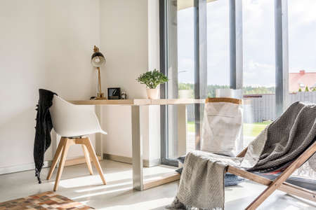 silla: Sala blanca con deckchair, escritorio de madera, silla y pared de ventana