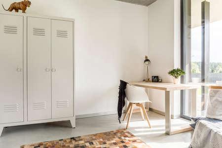 luz natural: interior de una casa blanca con armario de metal, escritorio y silla Foto de archivo