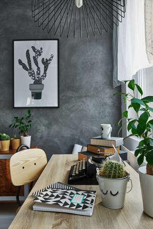 Kamer met grijze muur, houten tafel en eenvoudige stoel Stockfoto