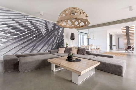 Pokój z dodatkową dużą sofę, drewnianym stołem i fototapety