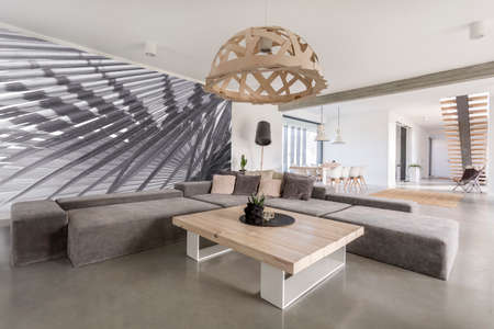 Zimmer mit extra großen Sofa, Holztisch und Fototapete Standard-Bild - 68553787