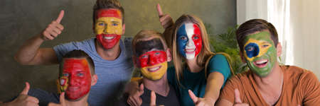 smiled: Multinational sport fans with national flags colours painted on their faces and their thumbs up