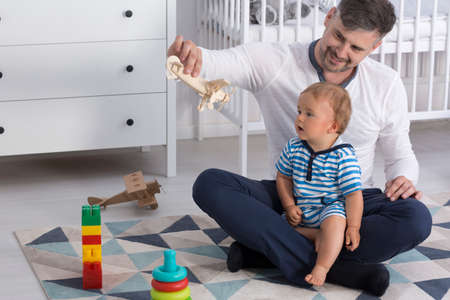 fondness: Father sitting on the floor with his child and showing him a wooden plane