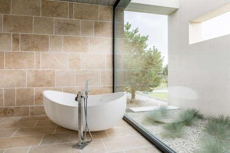 bathroom wall: Bathroom with window wall, bathtub and beige tiling