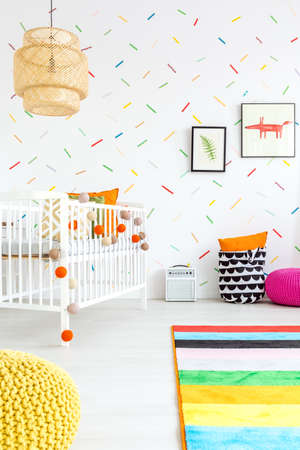 wall decor: Baby room with colorful wall decor and white cot
