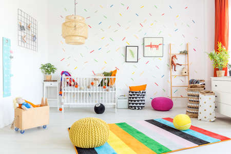 Baby room with white wall and light wooden furniture Фото со стока
