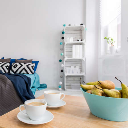 coffees: Stylish bedroom in scandynavian style with large bed, two coffees standing on wood table Stock Photo