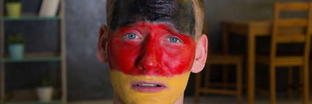 Close shot of a mans face painted in German flag colours