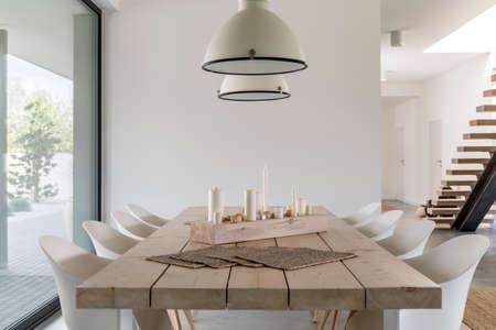 Camera con tavolo da pranzo in legno, sedie bianche e lampada industriale Archivio Fotografico - 68553837
