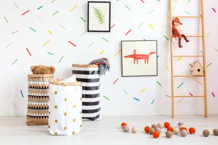 Witte kinderkamer met decoratieve katoenen ballen en speelgoed