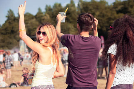 open air: Group of three young friends having fun during an open air concert