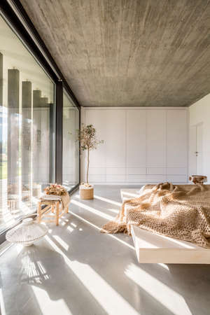 Light bedroom with window wall, bed and wooden ceiling