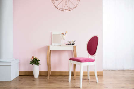 mirror on wall: Pink room with column, dressing table and upholstered chair