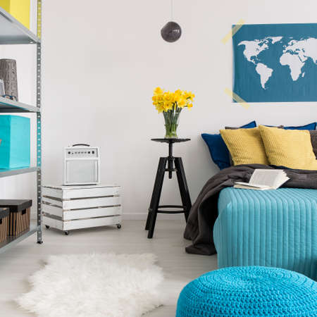 pouffe: Cozy bedroom with large bed, decorative pillows and blue pouffe with light walls