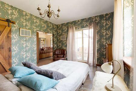 comfort room: King-size bed in rustic bedroom with elegant green wallpaper