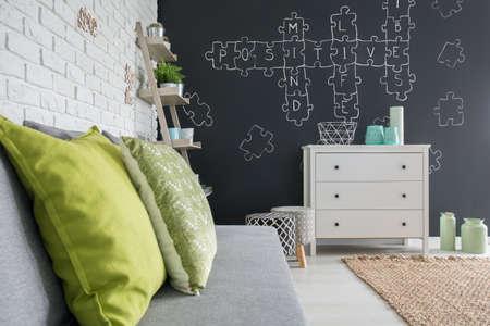 wall decor: Living room with chalkboard decor, sofa, dresser and brick wall Stock Photo