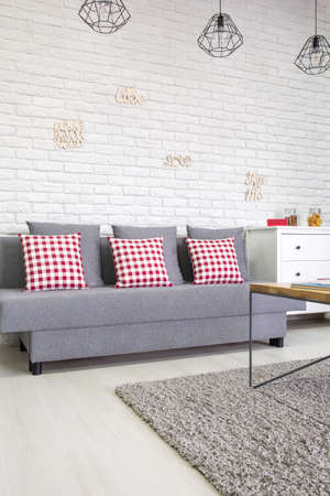 red pillows: Living room with sofa, red pillows and white brick wall