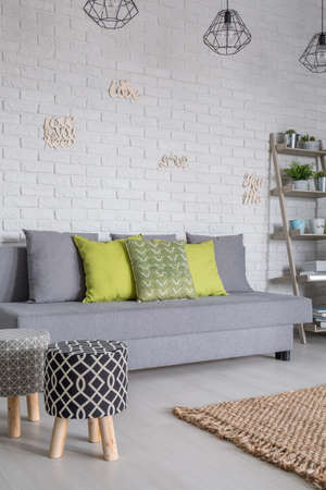 upholstered: Living room with sofa and upholstered stools Stock Photo