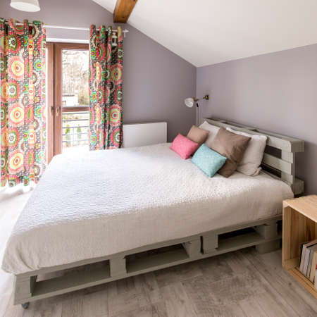 kingsize: King-size pallete bed in a modern grey bedroom with colourful curtains Stock Photo