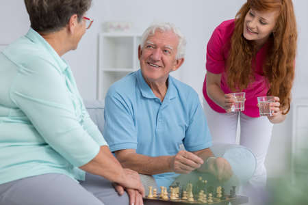 Caregiver bringing water to elderly couple playing chess Stock Photo