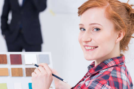 cooperate: Close shot of a young and red haired woman designer keeping the color picker and pencil in her hand and smiling