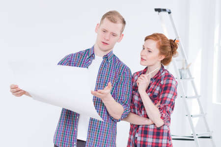 Young man and woman looking at house project in bright interior with a ladder during renovation