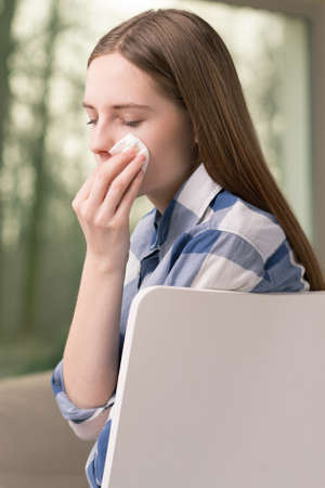 doldrums: Sad teenage girl crying and wiping tears with a tissue Stock Photo