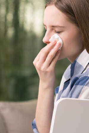 Sad young girl wiping tears with white tissue after hard day at school Stock Photo