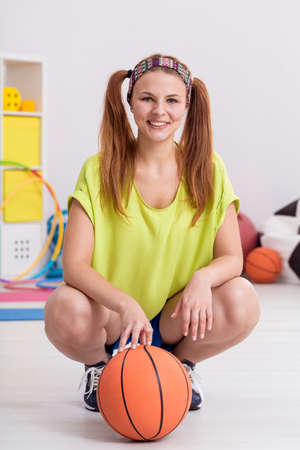 en cuclillas: Smiling basketball player squatting in a room behind a basketball