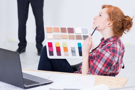 picker: Young and red haired woman designer sitting thoughtful at a desk with a laptop on, color picker in her hand