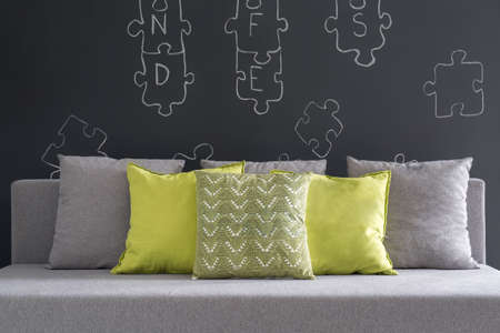 wall decor: Room with puzzle wall decor and sofa with green cushions Stock Photo