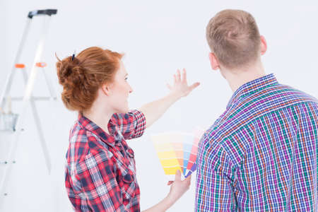 picker: Young man and woman choosing the wall colour by color picker in womans hand, with a ladder at the background Stock Photo