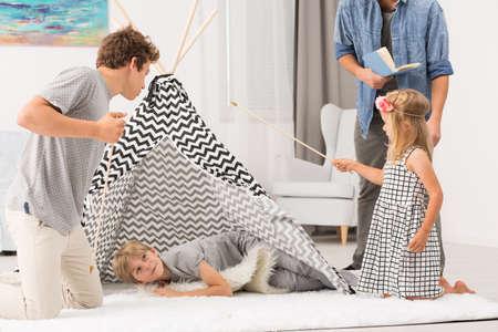 Familia feliz que juega en el suelo en la sala de estar
