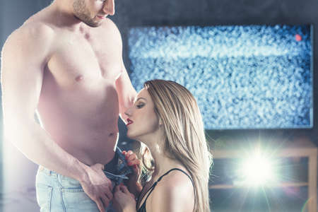 erotic fantasy: Erotic dressed woman with red lips unzipping mans trousers