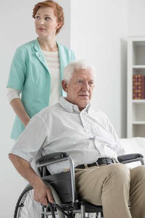 common room: Upset senior on wheelchair with nurse standing behind
