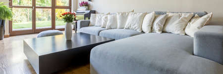 extra large: Room with extra large sofa, small tableand balcony door Stock Photo