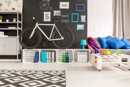 room wall: Black and white student room with bicycle, blackboard and sofa