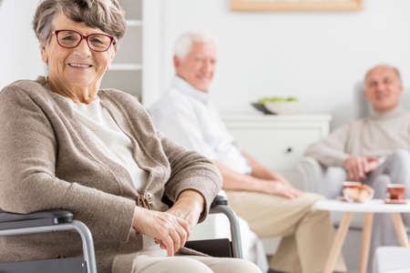 common room: Smiled woman on a wheelchair at nursing home Stock Photo