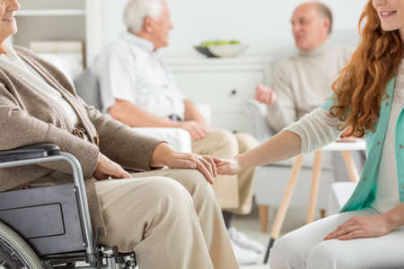 common room: Nurse supporting the charge at nursing home Stock Photo