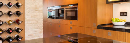 wall mounted: Kitchen with light wooden cupboards and wall mounted wine rack