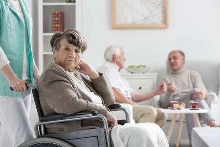 nursing care are for seniors: Upset senior woman on wheelchair in nursing home Stock Photo