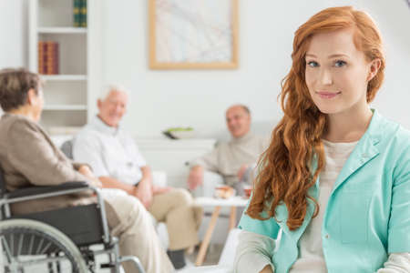 home keeping: Young and red-haired nurse at retirement home