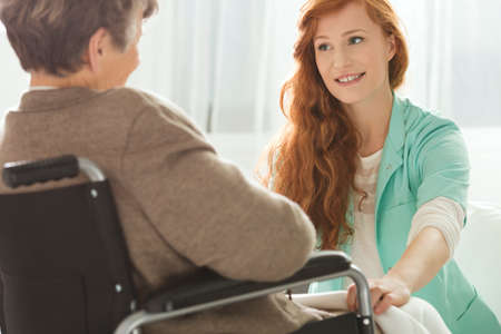 common room: Supportive young nurse looking at elder woman
