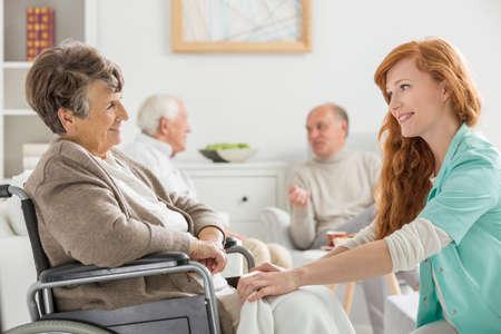 車椅子の年配の女性の世話を看護師します。 写真素材