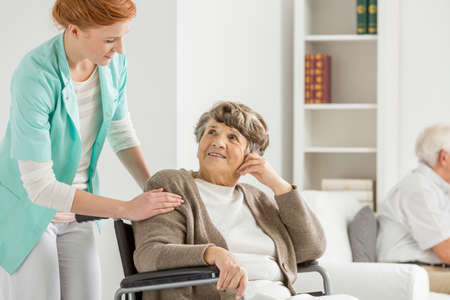 Woman on wheelchair looking at her young nurse Stock Photo