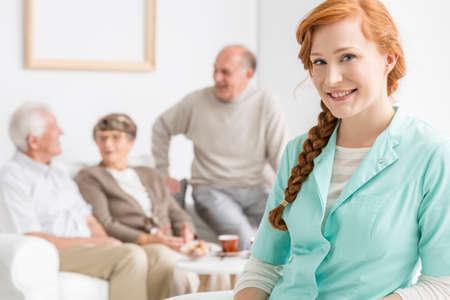 Glimlachte verpleegkundige in bejaardentehuis met senioren