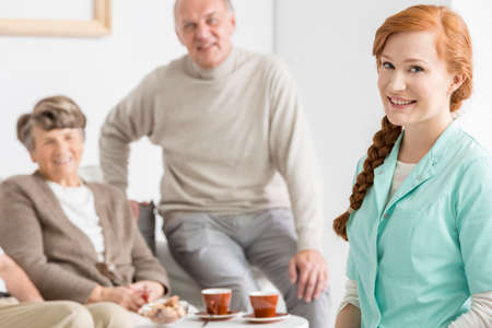 smiled: Smiled elder charges with their red-haired nurse Stock Photo